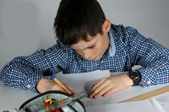 Boy doing maths homework. Concentrated teenager boy sitting at his desk  doing his maths school  homework Stock Photography