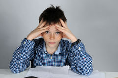 Boy doing maths homework. Concentrated teenager boy sitting at his desk  doing his maths school  homework Stock Images
