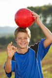 Boy doing okay sign with soccer ball. Royalty Free Stock Images