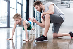 Boy doing push ups with coach. At fitness center Royalty Free Stock Photos