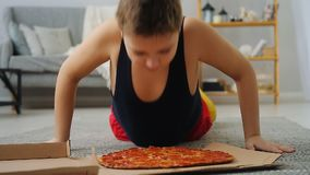 Boy doing push-UPS from the floor where the pizza is stock footage