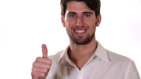 A boy doing thumb-up sign over white background stock footage