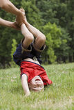 Boy doing upside down. Young boy doing upside down on green grass Royalty Free Stock Images
