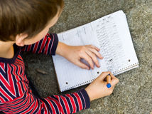 Boy doing writing homework. Looking down on book writing letters in book Royalty Free Stock Photo