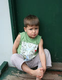 Boy on doorstep. Young boy sitting on the doorstep with bare feet and worried look Royalty Free Stock Photos