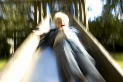 Boy down the slide. A boy coming down the slide. picture with moving blur in it royalty free stock photos
