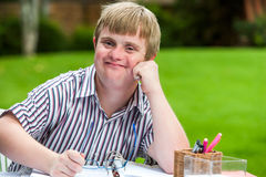 Boy with down syndrome at desk holding glasses. Stock Photos