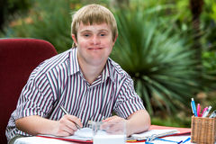 Boy with down syndrome at desk outdoors. Close up portrait of young male student with down syndrome at study desk outdoors Royalty Free Stock Photography