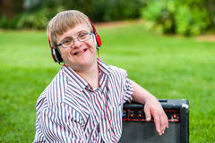 Boy with down syndrome wearing headphones. Close up portrait of young man with down syndrome wearing headphones outdoors Royalty Free Stock Photo