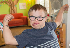 Boy With Downs Syndrome Flexing His Muscles Royalty Free Stock Photos
