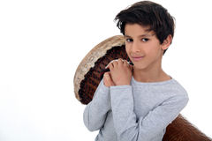Boy dragging giant drum Stock Photography