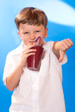 The boy drank a beverage a tubule. The boy did not like a beverage in a glass Stock Image