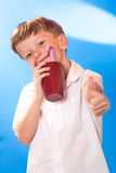 The boy drank a beverage a tubule. The boy very much liked juice in a glass Royalty Free Stock Images