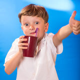 The boy drank a beverage a tubule. The boy very much liked juice in a glass Royalty Free Stock Photos