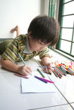 Boy drawing. Boy lying on the floor and drawing on the art paper Stock Photography