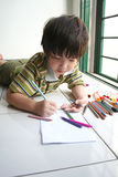 Boy drawing. Boy lying on the floor and drawing on the paper Stock Photography