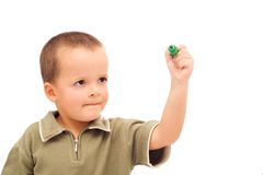 Boy drawing. With a green marker, very attentive, eyes wide open in wonder - isolated Royalty Free Stock Photography