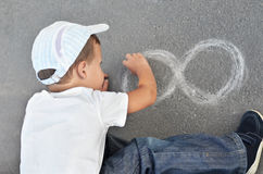 Boy drawing on asphalt Stock Photography