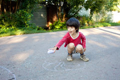 Boy drawing on asphalt Stock Photos