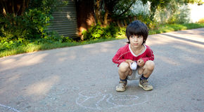 Boy drawing on asphalt Royalty Free Stock Image