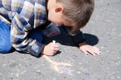 Boy drawing on asphalt in spring, child paint crayons Stock Image