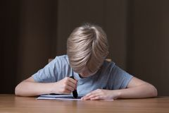 Boy drawing with black crayon Royalty Free Stock Image