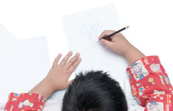 Boy drawing cartoon on white paper. On white background royalty free stock photos