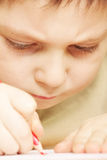 Boy drawing closeup. Little boy drawing with red pencil closeup photo Royalty Free Stock Images