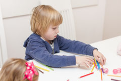 Boy drawing with colorful crayons Stock Images