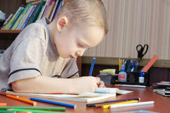 Boy is drawing with colorful pencils in a book Royalty Free Stock Images