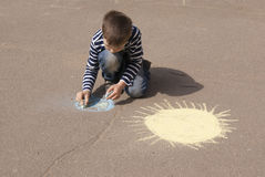 Boy drawing Earth and sun Stock Photos