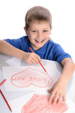 Boy drawing a heart that says I love mom Royalty Free Stock Photos