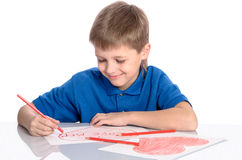 Boy drawing a heart that says I love mom Stock Image
