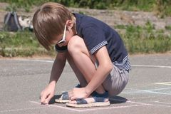 Boy is drawing hopscotch on the asphalt. Boy is drawing hopscotch on the asphalt royalty free stock photo