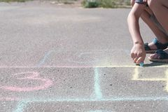 Boy is drawing hopscotch on the asphalt. Close-up hand and legs. Boy is drawing hopscotch on the asphalt royalty free stock photography