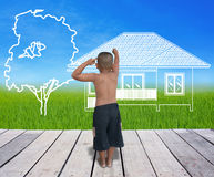 Boy drawing the house with tree on lanscape Royalty Free Stock Photos