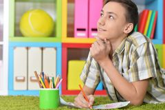 Portrait of boy drawing while lying on floor royalty free stock photo