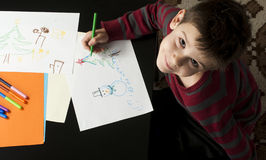 Boy drawing with markers. Multicolored papers Royalty Free Stock Image