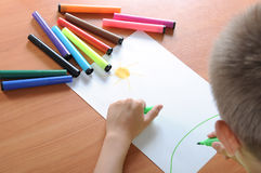 Boy drawing on paper with crayons Stock Photos