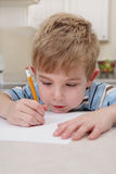 Boy drawing with a pencil royalty free stock photo