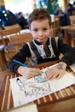 Boy drawing with pencil. In a cafe Stock Photo
