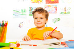 Boy drawing with pencil on the paper at table. Boy drawing with pencil on the paper while sitting at the table with drawings on background Royalty Free Stock Photo