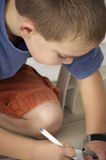 Boy drawing a picture. Close-up of a boy drawing, focus on head Stock Image