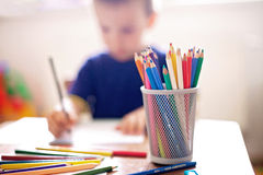 Boy, drawing a picture, pencils on focus Stock Photo