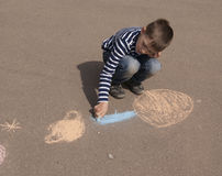 Boy drawing planets outside Stock Images