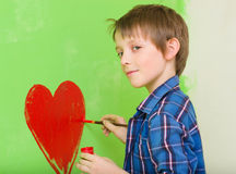 Boy drawing red heart. Cute boy drawing red heart on the wall at home Stock Photo