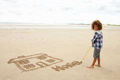 Boy drawing in sand. Smiling at camera royalty free stock photography