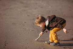 A boy is drawing on the sand with a stick Royalty Free Stock Photo
