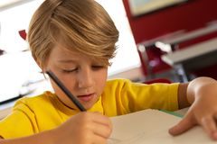 Boy drawing sketch on book at desk in a classroom. Front view of Caucasian boy drawing sketch on book at desk in a classroom at elementary school royalty free stock photo