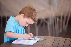 Boy drawing or writing. Little boy drawing or writing at outdoor terrace stock image